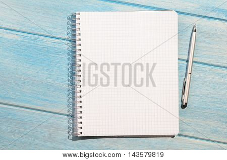 blank page of chequered notepad with pen on blue wooden table