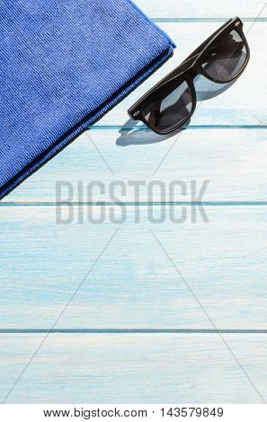 beach accessories. stylish sunglasses with towel on blue wooden table