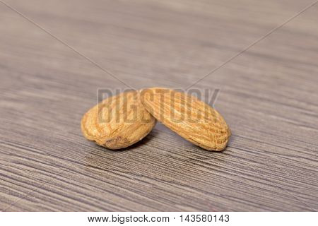Almond isolated on wooden background in studio