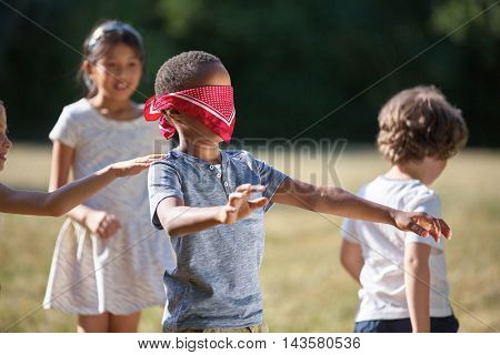 Children playing blind man's buff in summer and having fun