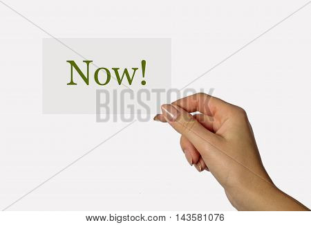 Beautiful hand of a young girl holding a card on a white background with the inscription Now!