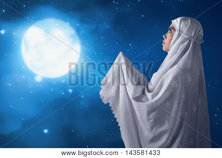 Asian muslim woman pray to god with the moonlight background.