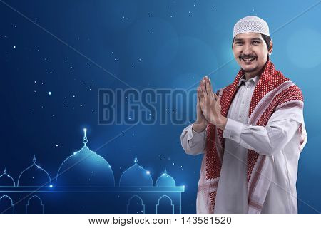 Young Asian Muslim Man Wearing Cap And Neat Dress And Mosque Logo Background.
