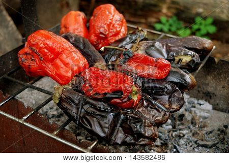 big red pepper and eggplants are baked on a lattice in charcoal