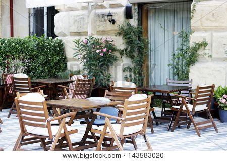Wood tables, wood chaires  and flowers at the restaurant cafe bistro terrace
