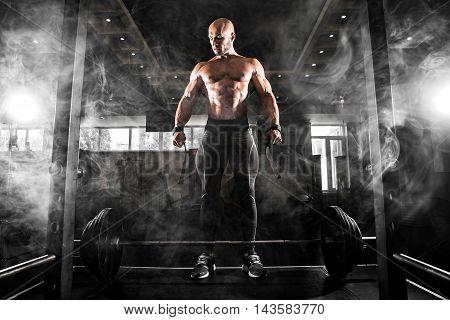 Bodybuilder preparing for deadlift of barbell. Smoke