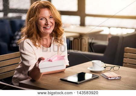 It is for you. Happy and smiling senior woman sitting at the table with cup of coffee, tablet and copybook while holding a gift