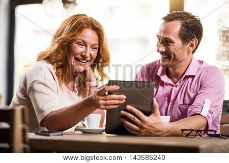 Unbelievable. Cheerful and delighted man and woman having fun and using digital tablet together