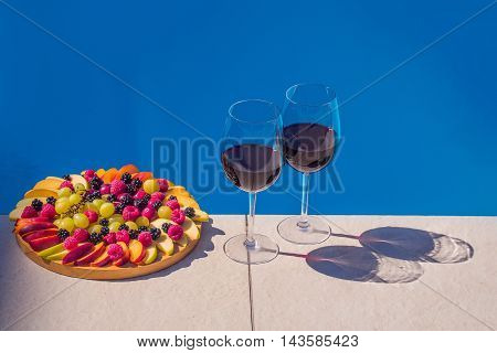 Fruit and berry platter with juicy ripe fresh tasty vibrant natural colorful dessert peach grape apple near two glasses of red wine on background of blue water copy space