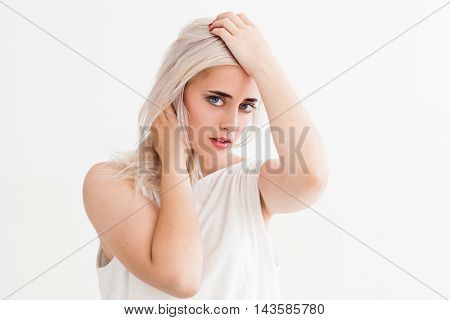 Frustrated young woman touching her head, looking at camera. Feeling stressed beautiful blonde with problems, white background