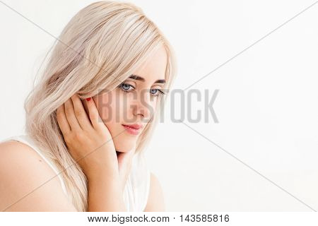Beautiful blonde with tranquil look on her face. Young pensive woman with family issues thinking about something, copy space, white background