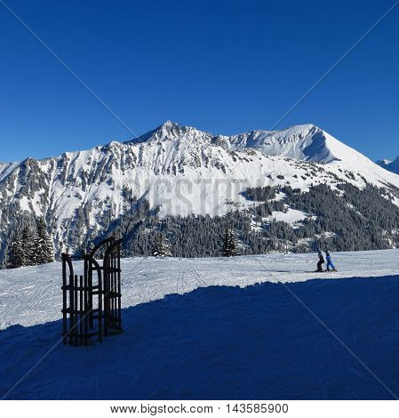 View from the top of Mt Wispile. Mt Lauenenhorn. Sledge and skier. Winter scene in Gstaad Swiss Alps.