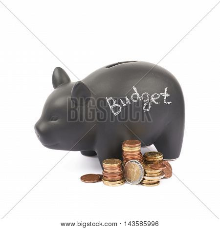 Word Budget written with chalk on a black ceramic piggy bank coin container next to a pile of euro coins, composition isolated over the white background