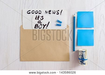 It's a boy greeting card in envelope, flat lay. Top view on kit of envelope with note, pencil, money and sticker on white background. Newborn congratulations mockup