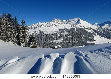 Landscape in Gstaad Swiss Alps. Snow shaped by wind and Mt Lauenenhorn. Firs.