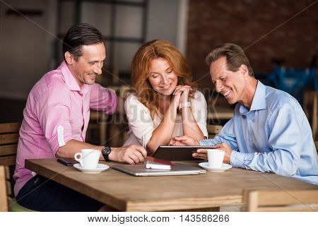 Workforce. Smiling and cheerful coworkers having informal meeting in a cafe