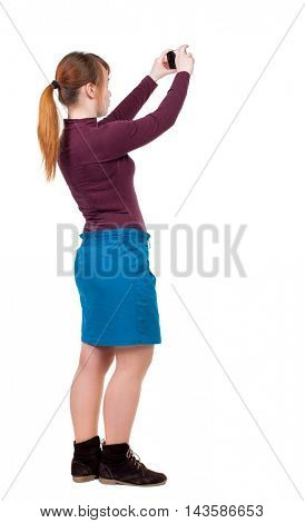 back view of standing young beautiful  woman  and using a mobile phone. girl  watching. Rear view people collection.  backside view of person.  Isolated over white background. Girl with red hair tied