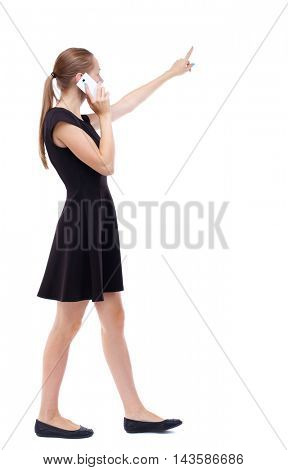 side view of walking  woman. beautiful girl going, pointing and talking on smartphone.  backside view of person.  Rear view people collection. Isolated over white background. Blonde in a short black