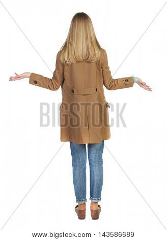 Back view of angry young woman Rear view. isolated over white. backside view of person.  Rear view people collection. Isolated over white background. The blonde in a brown raincoat, surprised her arms