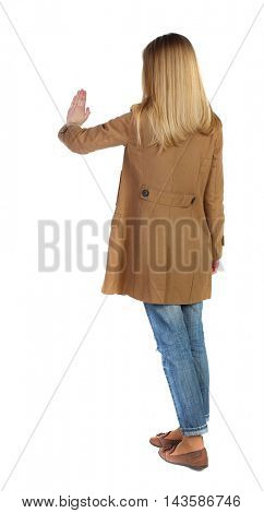 back view of woman. Young woman presses down on something. Isolated over white background. Rear view people collection. backside view of person. The blonde in a brown cloak presses his hand on the