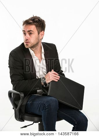 Tired manager sitting on chair covers laptop so that you can not see what he was working with fright looking at right. Studio, white background.