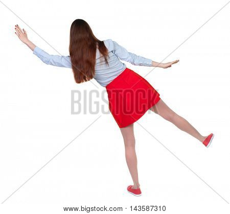 Balancing young woman.  or dodge falling woman. Rear view people collection.  backside view of person.  Isolated over white background. Long-haired brunette in red skirt falls to the side.