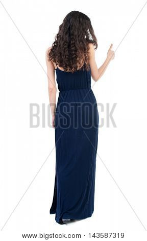 Back view of  woman thumbs up. Rear view people collection. backside view of person. Isolated over white background. The dark curly girl in blue evening dress shows thumb up.