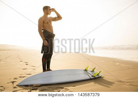 A surfer with his surfboard looking to the waves