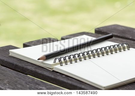 Closeup photo of notebook with old golden ink pencil at wood background