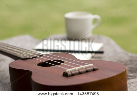 blurred ukulele with cup of coffee and notepad on green background