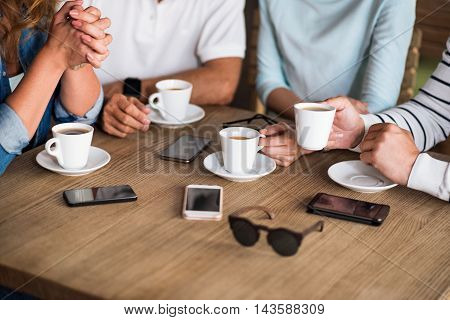 Keep in touch. Close up of table with cups of coffee, mobile phones and sunglasses on it