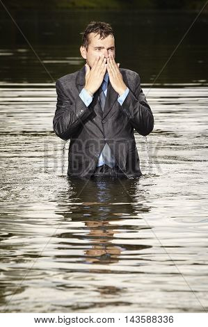 Crazy businessman in suit leaving water in river