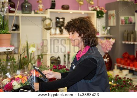 Happy Middle Aged Woman Chooses Plant At Flower Shop