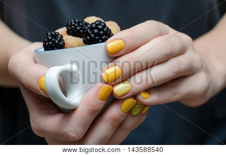 Female hand with yellow nail design holding a cup with berries