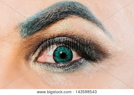 Male eye with decorative colored green contact lens dark eyeshadow makeup and hairy eyebrow with amazed look closeup