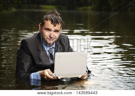 Crazy businessman in suit holding broken notebook