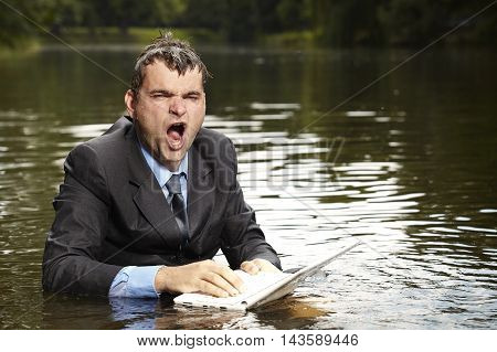 Crazy businessman in suit trying to save notebook