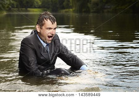 Crazy businessman in suit and tie swimming after burning out