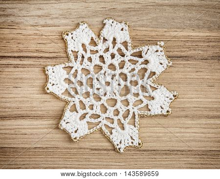 White crochet christmas decoration on the wooden background. Christian holiday. Symbolic object.