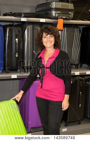 Confident Woman Selecting Travel Suitcase In A Shop