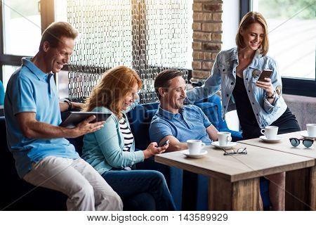 New technology. Positive and delighted people using their smart phones and digital tablet while relaxing in cafe
