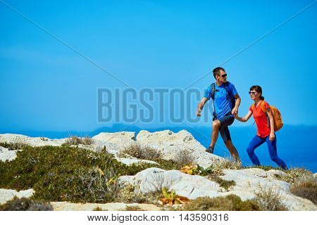 couple of travelers with backpack standing on the cliff against sea and blue sky at early morning