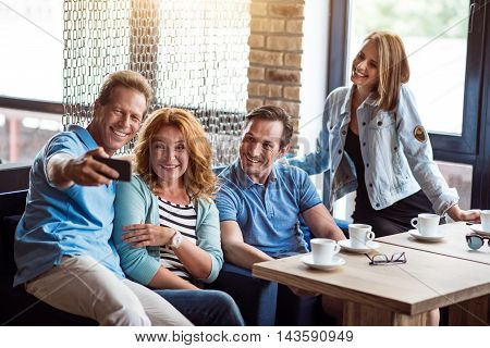 Positive one. Delighted and content group of people taking selfie photo while drinking coffee in cafe