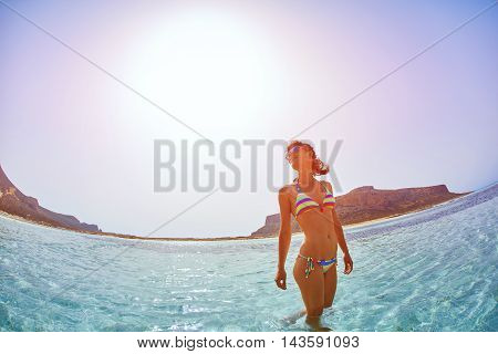 beautiful sexy woman dressed in bikini walking on the beach along the sea front