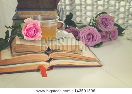 Pile of vintage books with bouqet of pink and violet rose flowers, retro toned