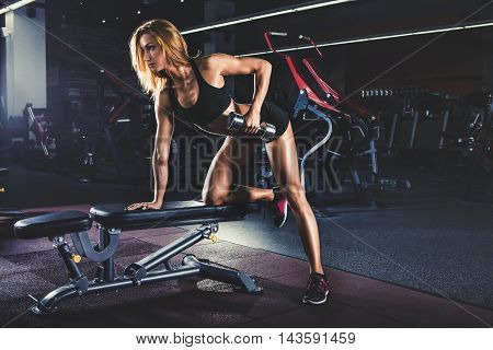 Young sexy girl pumping up muscles with dumbbells