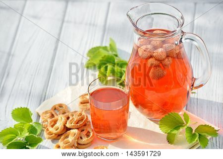 Homemade strawberry compote in glass decanter with pretzels on white wooden table in garden. Freesh fruit drink