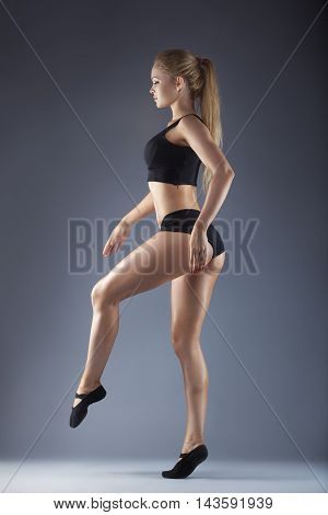Ballerina in black outfit posing on toes over grey studio background.