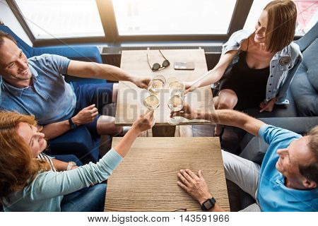 Yummy drink. Top view of delighted and smiling friends holding glasses of champagne and having little party