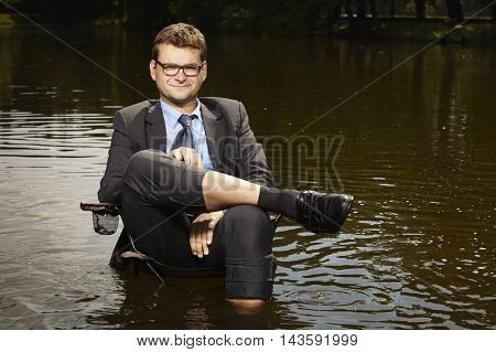 Businessman in suit relaxing after burning out deep in water